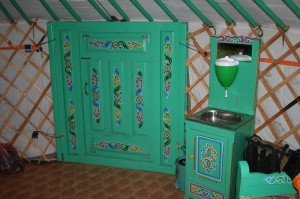 The entrance to the yurt from the inside. To the right of the door is the wash basin. The receptacle above the basin can be filled with water. The waste water flows into a bucket underneath the basin.